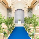 【チャペル】~80名 ウォーターカーテンの祭壇に、純白のドレスがまばゆく映えるブルーのバージンロード。祭壇を流れる水が光を受けてきらきらと輝き、幻想的なシーンを描きます。