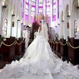 大聖堂に合うようにデザインされた他にはない純白のロングトレーン。バージンロード20mと地域最大級の大聖堂との相性は抜群。