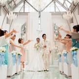 ゲストからの祝福の歓声とフラワーシャワーが挙式を盛大に彩る。たくさんの笑顔に囲まれ、幸せを改めて実感
