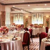 披露宴会場【アカンサス】はステンドグラスの飾り窓や天井で、広がりを感じられる空間。 新郎新婦とゲストが一緒に楽しめる空間では、とてもアットホームなパーティーに。 それでいて、大人の余裕も感じられる会場。