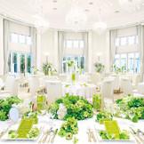 大きな窓から差し込む陽光で明るい会場。様々なコーディネートが似合う白亜の邸宅【アヴェニュー】 扇状に広がるバンケットは、アイボリー調で温かみのある空間。天井が高く、その大きな窓からは明るい光が降り注ぎます。
