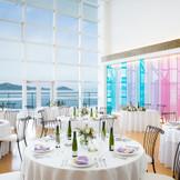 藍色、孔雀青、薄桜…。時間ごとに繊細に色を変える海と空を表現した淡い色調のガラスアートが海の情景と美しく重なり合う。一面ガラス窓の広々とした開放感に溢れる空間でマリンブルーを眺めながら、ゲストに感謝を伝えて。