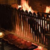 お客様の目の前で焼かれるメイン(お肉)料理。本物の薪を使用した暖炉の風情を味わえる。