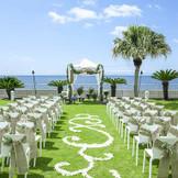 鮮やかな芝生のグリーンが、美しい『アクア ガーデン』専用ガーデンは海を眺めながら挙式セレモニーが可能。挙式以外にもパーティを楽しむスペースとしても絶好のロケーション! シーサイド リビエラの会場設備の写真