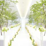 陽光が差し込むアレンジ自由な純白のチャペル。木々を飾れば、陽の光に照らされた新緑の中での挙式も叶う。