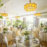 柔らかな自然光が降り注ぐガーデンビューの披露宴会場。130名までゆったりと着席でき、大人数のパーティーも安心。隣にはガーデンを臨むプライベートリビングルームも併設。