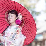 淡いピンクの打掛に合わせた2種類のダリアのヘッドドレス。濃淡が美しく花嫁を輝かせる。朱色の傘を小物に使って印象的な写真を残してみては