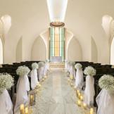 聖歌隊の歌声とバージンロードを照らすキャンドルの光の中で感動挙式を…