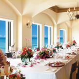 窓の外に、きらめく読谷の海が広がるパーティ会場。大きなテーブルをゲスト全員で囲めば、自然と会話も弾みそう。