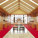 神殿の正面は大きなガラス張りに。 自然光が入る明るい空間は、花嫁の白無垢姿をより一層輝かせます。 天候・気候に左右されないゲストにも優しい屋内のスペースです。