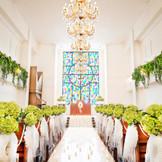 白×グリーンのチャペル。目の前には大きなステンドグラスがきらきらと輝く、あたたかみのあるチャペルです。