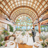 【ホルトゲストヴィラ(別棟)】開放的な吹き抜け空間。一面のガラス窓から光が降り注ぐ。窓の外には桜島、鹿児島市内の風景が広がる。