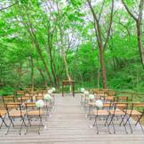 ホテルの敷地内を流れるせせらぎを目の前に、緑あふれる木々に包まれた森の中のセレモニー。