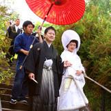 新郎新婦が手を取り合い歩む、花嫁行列