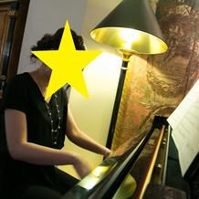 部屋のグランドピアノで演奏