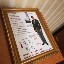 男子更衣室内。モーニングの着方説明。