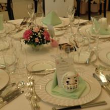 テーブルやクロスも淡く、ダルマの席札。