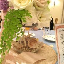 テーブル装花アップ。瓶の中に貝殻。