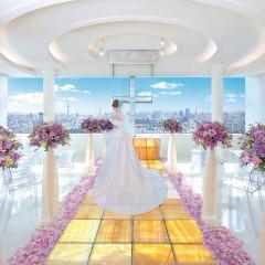 新郎新婦を天空へ誘う光り輝く天然石オニキスのバージンロードは、1枚1枚が世界で一つしかない特注品。目の前に広がるどこよりも東京らしい眺望に、ゲストからも歓声が上がるチャペル。
