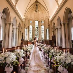 石造りの教会は重厚な扉を開けると、大理石のバージンロードが厳かな誓いの舞台へと導く。118年もの時を重ねたステンドグラスからの温かく神秘的な光に包まれて、永遠の誓いを