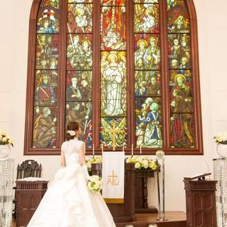歴史あるステンドグラスの光に包まれる2人の誓い。