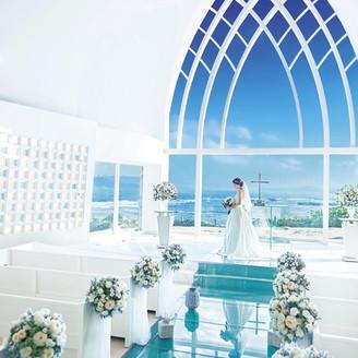 アクアルーチェ・チャペル。 全面ガラス張りになった祭壇のバックには、南国の景色が一面に広がります。白亜のチャペルに海と空の青がよく映えます