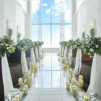地上60mのスカイチャペル。一面窓からは自然光がたっぷりと降り注ぐ開放的な空間。 白大理石のバージンロードは、ロングトレーンやベールが美しく広がり、歩く花嫁をより美しく輝かせる。