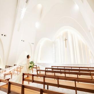 チャペル・ソルミエは10mを超える天井高と横に広いのが特徴。ゲストとの距離を縮めてアットホームなウェディングが叶う。純白のドレスも透明感があふれる