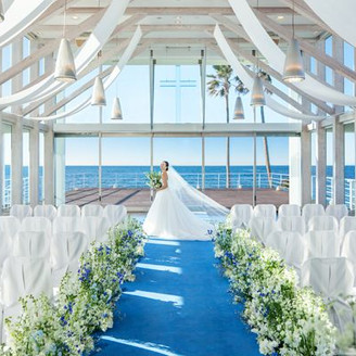 青く輝く海に三方向を囲まれた、透明感溢れるガラス張りの「シーサイド チャペル リビエラ」。明るい自然光で花嫁もより美しく映し出されます。