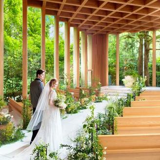 まるで森の中を歩むようなバージンロードの先には、ふたりの祝福を見守るシンボルツリー。自然が醸し出す神聖な雰囲気の「森の教会」