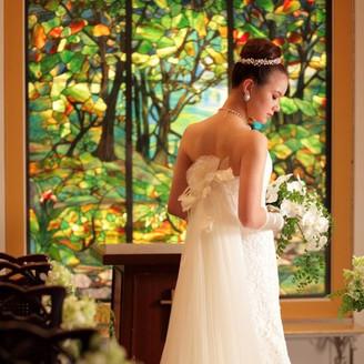 緑が溢れる木々をモチーフにしたステンドグラスの前ではウェディングドレスがより一層引き立つ。