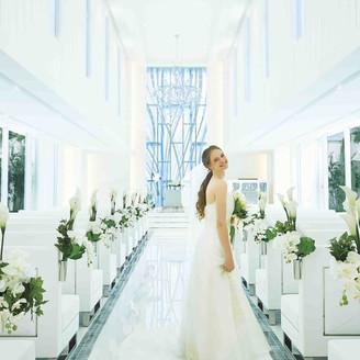 自然の光が注ぐ明るいチャペルでウェディングドレス姿が自然光に包まれる