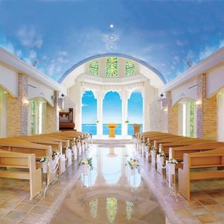 大きな3面ガラスに映る青い海と大空が、バージンロードを歩くお二人を幸せへと導きます♪ご参列席から見る景色はまるで海に浮いているような感覚です。沖縄でリゾートウェディング・フォトウェディングなら「リザン・ル・アンジュマリー教会」